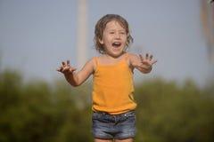 Маленькая девочка наслаждаясь светлым дождем лета стоковые фотографии rf