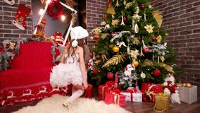 Маленькая девочка нашла подарки под рождественской елкой, дочерью в эльфе костюм ` s Санты выбирает сюрприз на Новый Год, рождест акции видеоматериалы