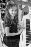 Маленькая девочка на белом рояле Стоковое Изображение RF
