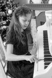 Маленькая девочка на белом рояле Стоковая Фотография