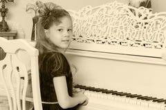 Маленькая девочка на белом рояле Стоковые Изображения RF