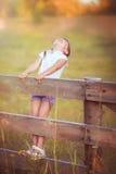 Маленькая девочка на загородке стоковая фотография rf