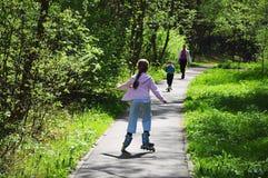 Маленькая девочка на коньках ролика в парке Стоковое Изображение RF