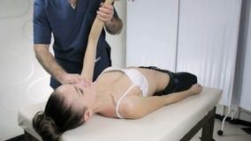 Маленькая девочка на приеме на хиропракторе доктора, анализе соединений рук акции видеоматериалы