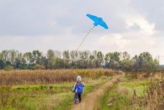 Маленькая девочка на пути дороги гравия поля бежать с змеем Стоковое Изображение RF