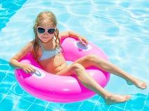 Маленькая девочка на раздувном кольце в плавательном бассеине Стоковые Фото
