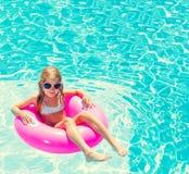 Маленькая девочка на раздувном кольце в плавательном бассеине Стоковая Фотография RF