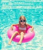 Маленькая девочка на раздувном кольце в плавательном бассеине Стоковое фото RF