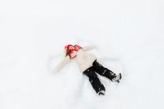 Маленькая девочка на снеге показывая диаграммы ангела Стоковые Фотографии RF