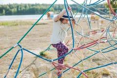 Маленькая девочка на спортивной площадке с лестницей веревочки Стоковые Фото