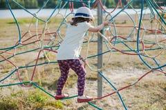 Маленькая девочка на спортивной площадке с лестницей веревочки Стоковое Изображение