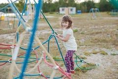 Маленькая девочка на спортивной площадке с лестницей веревочки Стоковая Фотография