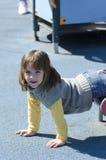 Маленькая девочка на спортивной площадке Стоковые Изображения RF