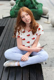 Маленькая девочка на стенде с телефоном Стоковая Фотография