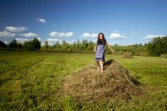Маленькая девочка на стоге сена в деревне Стоковые Фото