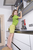 Маленькая девочка на стуле, который нужно достигнуть более высоко для того чтобы получить шоколады Стоковые Изображения RF