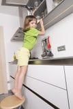 Маленькая девочка на стуле, который нужно достигнуть более высоко для того чтобы получить шоколады Стоковое Изображение