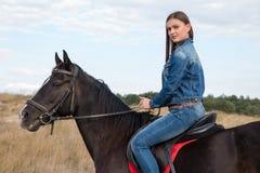 Маленькая девочка на темной лошадке Стоковое Изображение RF