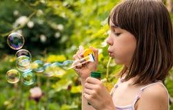 Маленькая девочка надувает пузыри мыла в саде Стоковое фото RF