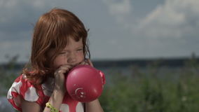 Маленькая девочка надувая воздушный шар сток-видео