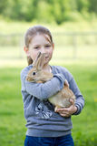 Маленькая девочка на улице для того чтобы держать кролика в реальном маштабе времени Стоковые Изображения RF