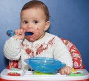 Маленькая девочка независимо ест с ложкой стоковое фото rf