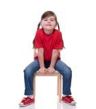 Маленькая девочка нося красную футболку и представляя на стуле Стоковое Изображение RF