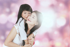 Маленькая девочка обнимает ее мать от задней части Стоковые Фотографии RF