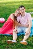 Маленькая девочка обнимая парня сидя на голубом одеяле Стоковая Фотография RF