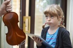 Маленькая девочка довольно сыграла бы на таблетке цифров чем практикует Vio стоковое изображение rf