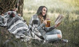 Маленькая девочка около дерева читая книгу Стоковое Изображение RF