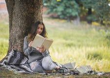 Маленькая девочка около дерева читая книгу Стоковые Изображения