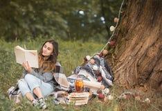 Маленькая девочка около дерева читая книгу Стоковая Фотография