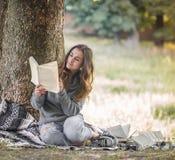Маленькая девочка около дерева читая книгу Стоковые Фотографии RF