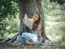 Маленькая девочка около дерева читая книгу Стоковая Фотография RF