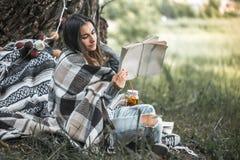 Маленькая девочка около дерева читая книгу Стоковые Фото