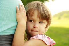 Маленькая девочка около живота его беременной матери на природе Стоковые Фото
