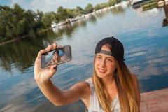 Маленькая девочка около реки принимая Selfie Стоковое фото RF