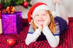 Маленькая девочка около рождественской елки с подарками Стоковое фото RF