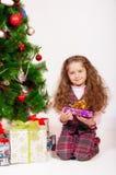 Маленькая девочка около рождественской елки с подарками Стоковые Фото