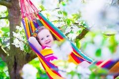 Маленькая девочка ослабляя в гамаке Стоковая Фотография