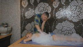 Маленькая девочка ослабляя с массажем пены в турецкой ванне видеоматериал