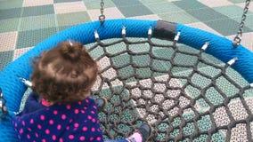 Маленькая девочка отбрасывая на сетчатом качании видеоматериал