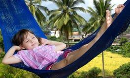 Маленькая девочка отдыхая в гамаке Стоковые Изображения