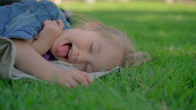 Маленькая девочка отдыхая на траве сток-видео
