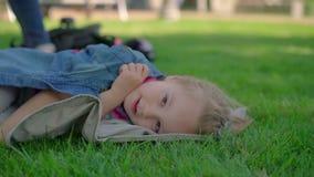 Маленькая девочка отдыхая на траве видеоматериал