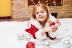 Маленькая девочка одетая как Санта с шариками рождества дома Стоковые Изображения RF