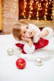 Маленькая девочка одетая как Санта с шариками рождества дома Стоковые Фотографии RF