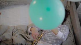Маленькая девочка одела в пижамах, приносит ваш пук мамы воздушных шаров других цветов Для потехи мама позволяет им вверх видеоматериал