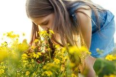 Маленькая девочка пахнуть желтым цветком Стоковые Фотографии RF
